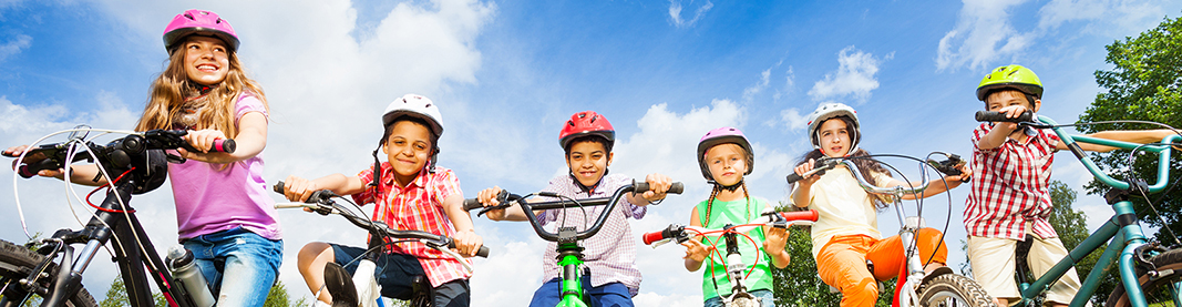 Below angle view of kids in helmets who hold their bikes and stand on path