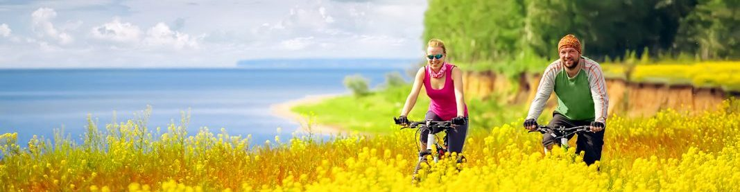 happy couple cycling in canola fields